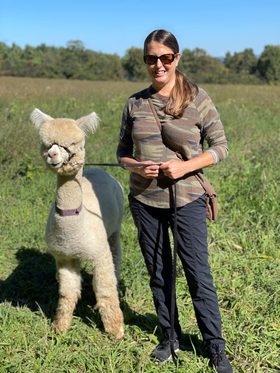 Woman in camouflage shirt and black pants standing next to a small white alpaca on a leash